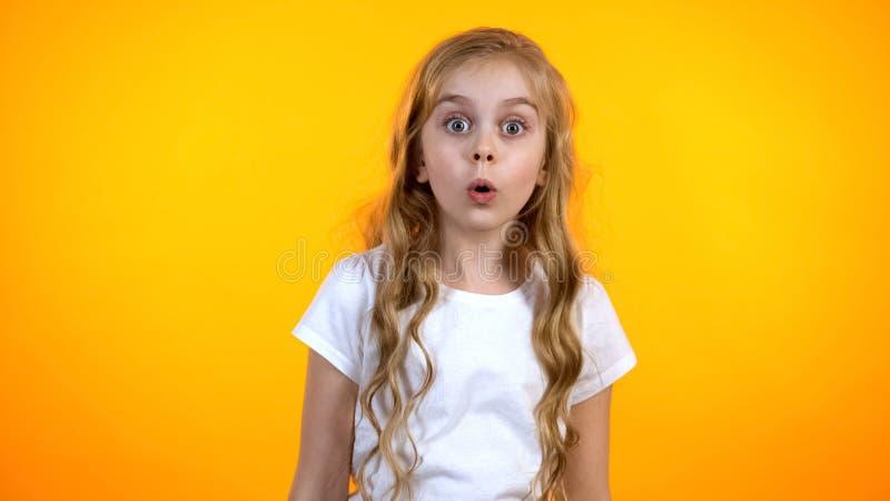 Surpreendeu extremamente a menina com os olhos grandes que olham à came, chocada com notícia, promo imagens de stock