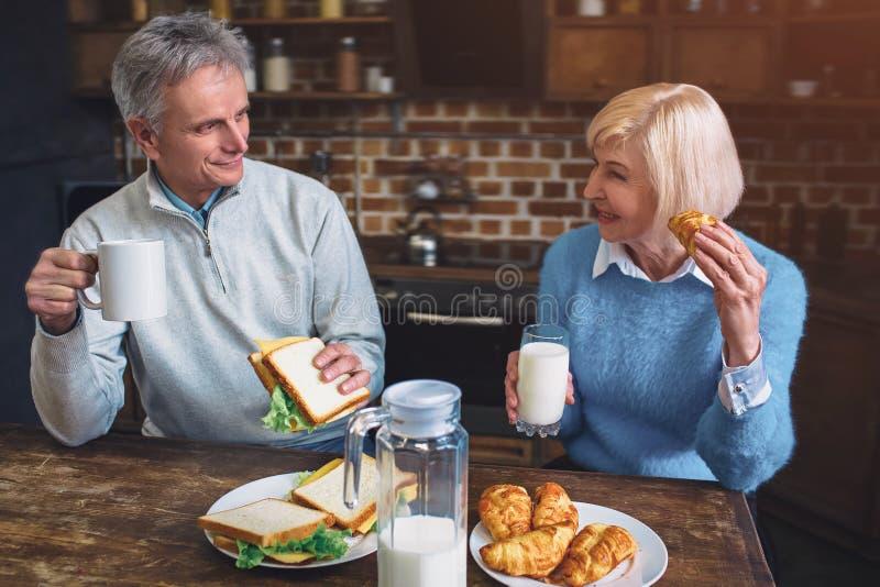 A surpresa e as pessoas adultas estão comendo a refeição na tabela na cozinha imagem de stock