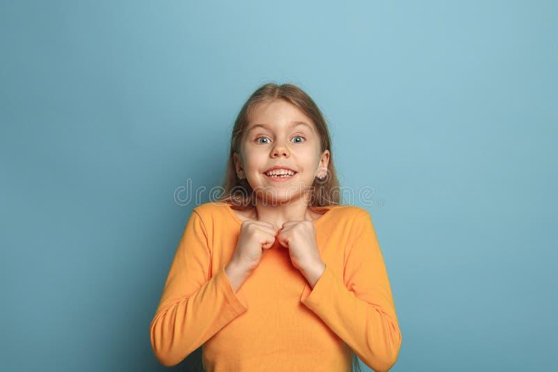 A surpresa, a felicidade, a alegria, a vitória, o sucesso e a sorte Menina adolescente em um fundo azul Expressões faciais e povo imagens de stock