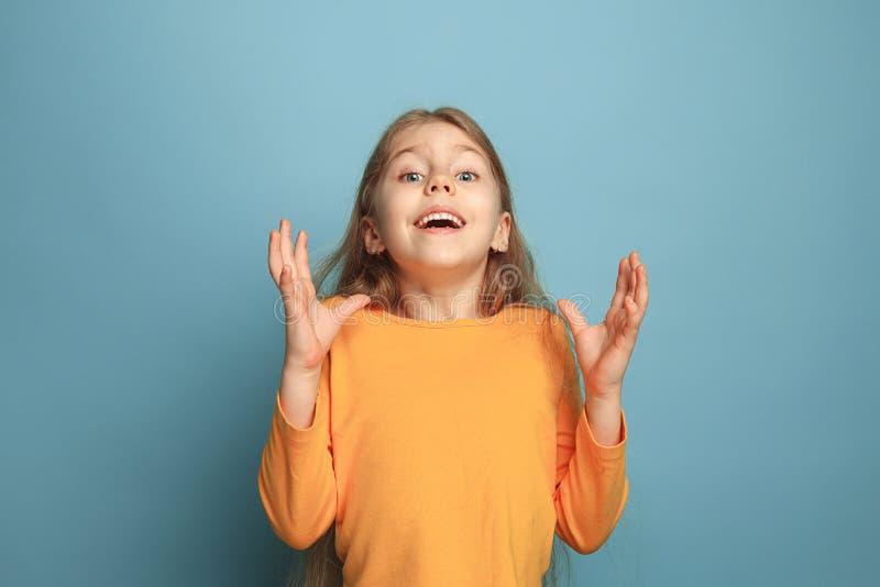 A surpresa, a felicidade, a alegria, a vitória, o sucesso e a sorte Menina adolescente em um fundo azul Expressões faciais e povo fotografia de stock