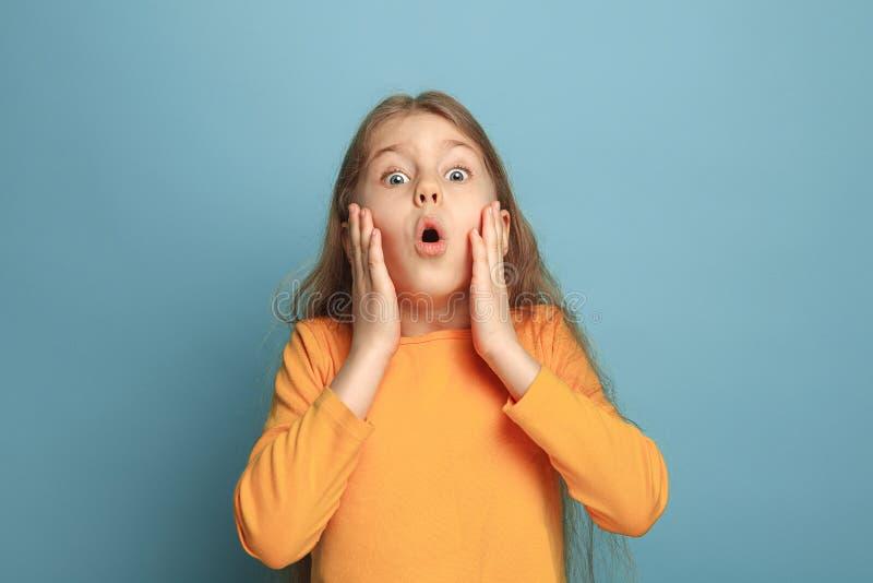 A surpresa, a felicidade, a alegria, a vitória, o sucesso e a sorte Menina adolescente em um fundo azul Expressões faciais e povo imagem de stock royalty free