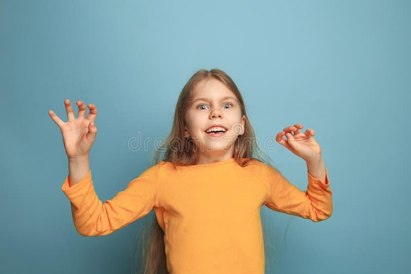 A surpresa, a felicidade, a alegria, a vitória, o sucesso e a sorte Menina adolescente em um fundo azul Expressões faciais e povo imagens de stock royalty free