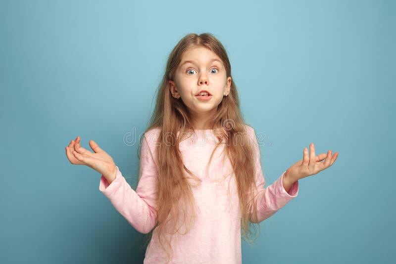 A surpresa, a felicidade, a alegria, a vitória, o sucesso e a sorte Menina adolescente em um fundo azul Expressões faciais e povo fotografia de stock royalty free
