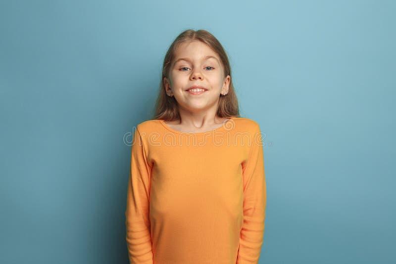 A surpresa, a felicidade, a alegria, a vitória, o sucesso e a sorte Menina adolescente em um fundo azul Expressões faciais e povo foto de stock royalty free