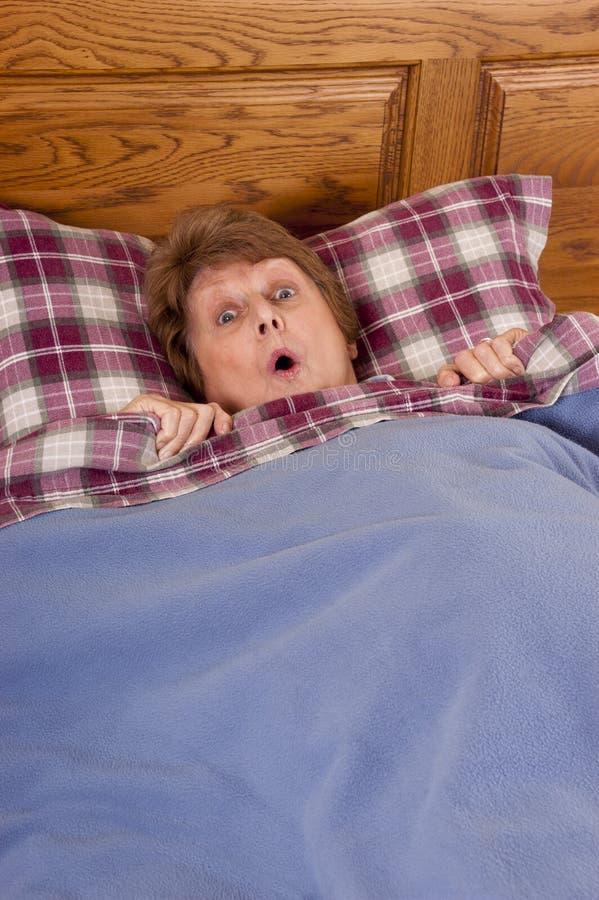 Surpresa sênior madura de choque da mulher na cama foto de stock