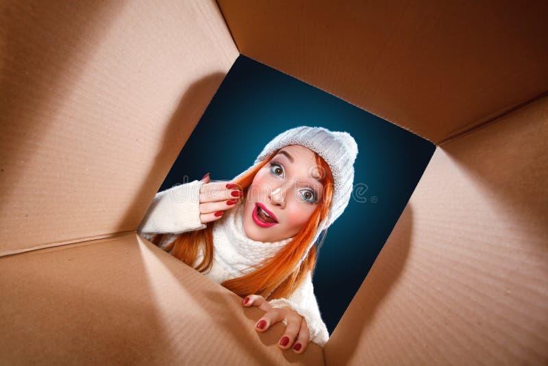 Surpriced jonge vrouw die een een kartondoos en binnen kijkend, verhuizing openen en concept uitpakken Giftaffiche met exemplaar royalty-vrije stock afbeeldingen