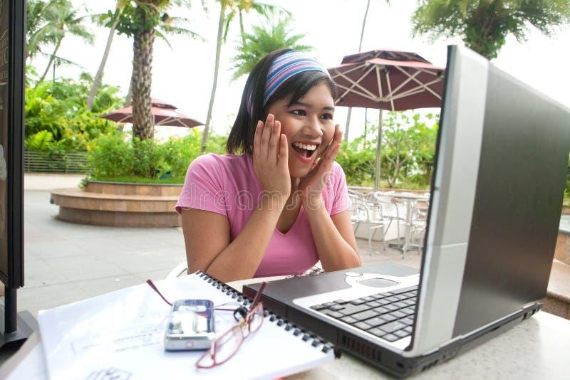 Surprise apparaissante d'étudiante devant l'ordinateur portable photographie stock libre de droits