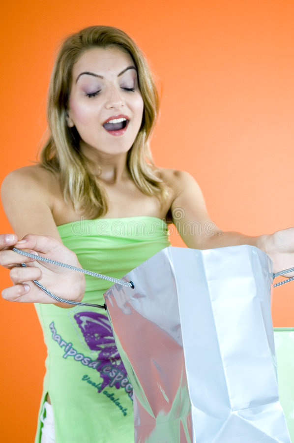 Surprise in a Bag. A woman receiving a surprise in a gift shopping bag stock photos