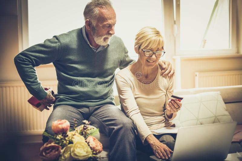 Surprise causes a smile. Senior couple at home with credit card and laptop. Senior men holding gift for his wife royalty free stock photo