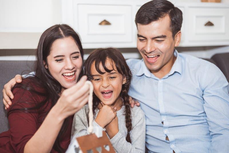 Surprise de père et de mère leur fille par le cadeau ou le nouveau jouet Les parents et les enfants sont heureux ensemble dans la image libre de droits