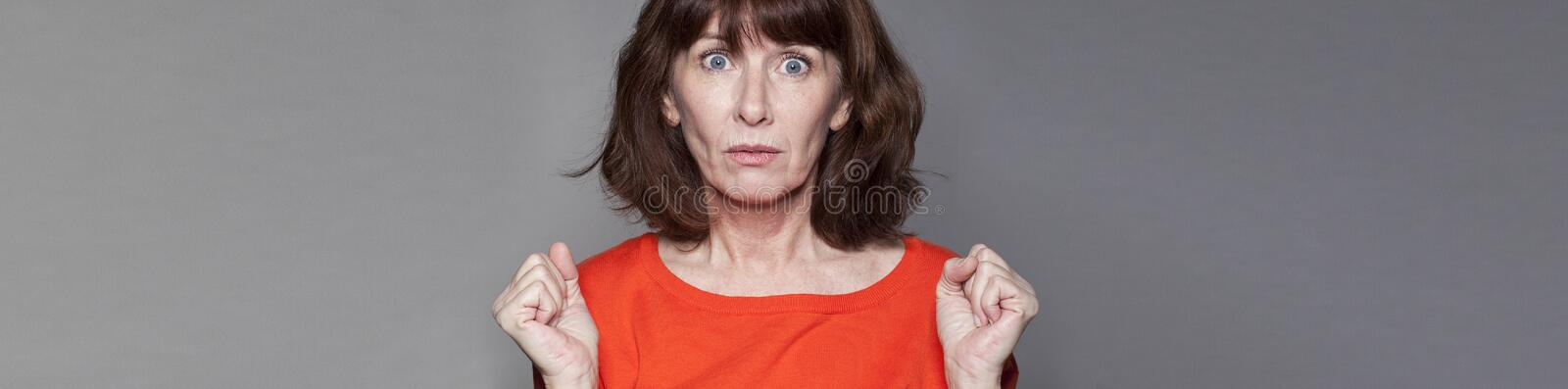 Surprised middle aged woman expressing misunderstanding, gray banner royalty free stock photos