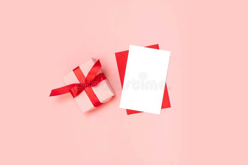 Surprise gift box wrapped in pink paper with a red bow, blank red envelope template on a pink background royalty free stock images