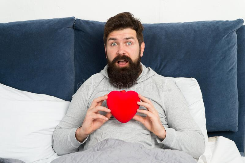Surprise gift. Holiday celebration. Happy morning. Bearded hipster need some love. Lack of love. Man relaxing in bed royalty free stock images