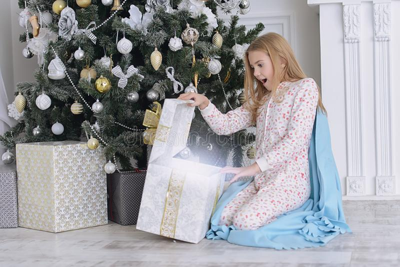 Surprise for girl. Pretty nine year old girl opens a gift box and surprises. Luxurious apartments decorated for Christmas. Merry Christmas and Happy New Year stock photography