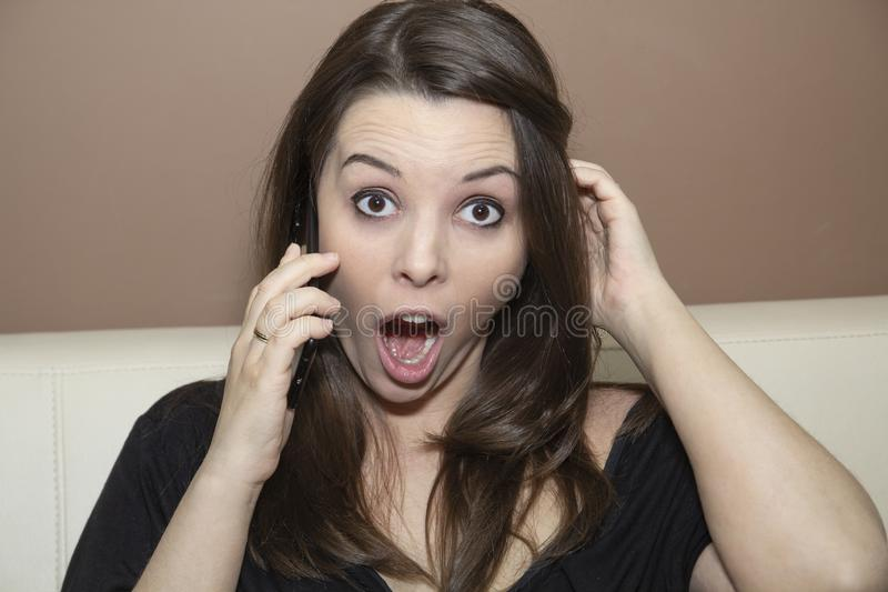 Surprise on her face during a telephone. stock photo