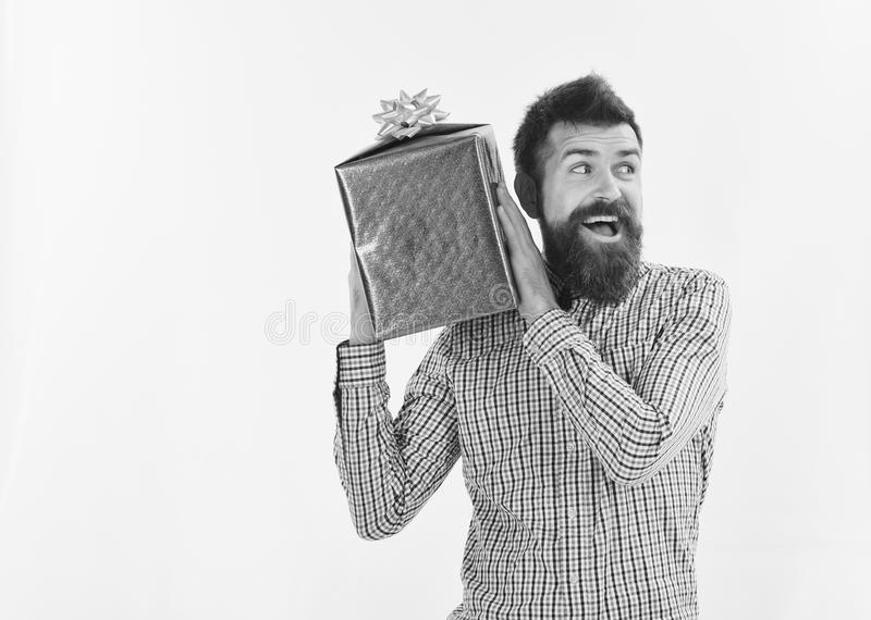 Surprise and holiday gift concept. Macho with wrapped blue gift. And white bow. Man with beard and excited face isolated on white background. Guy in plaid shirt stock images