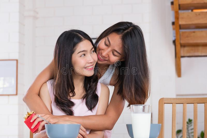 Surprise lesbienne asiatique de couples en donnant le cadeau pour l'anniversaire de l'amour au temps de petit déjeuner de cuisine image libre de droits