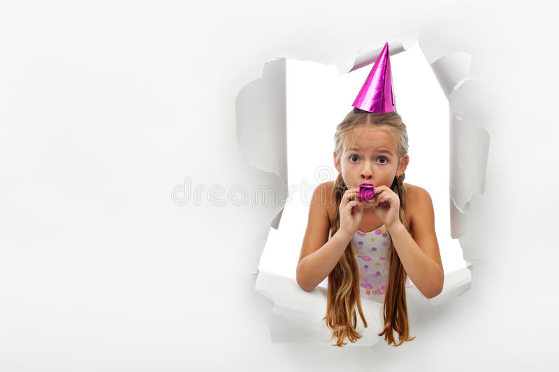 Surprise - little girl with party horn popping out from a torn p. Aper sheet - with copy space royalty free stock images