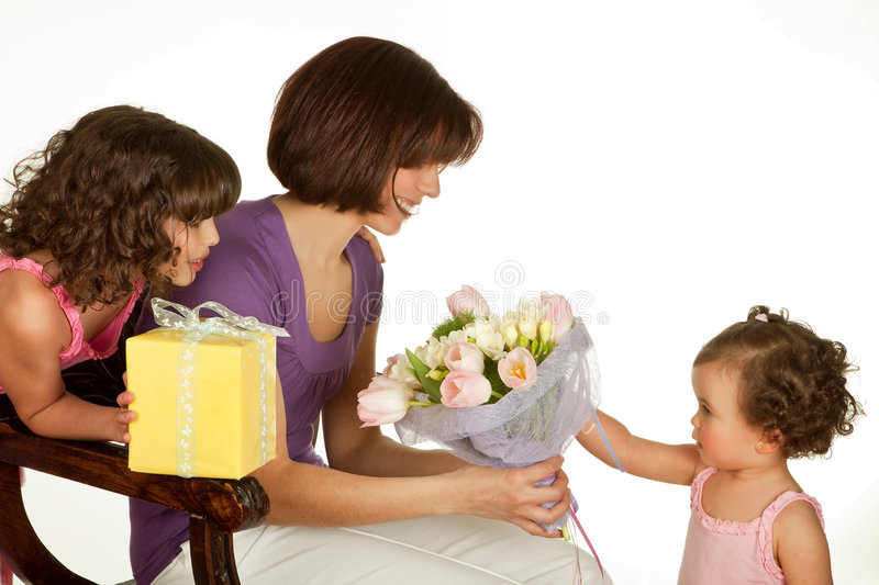 Surprise for mother. Two little girls giving flowers and gifts on mother's day royalty free stock images
