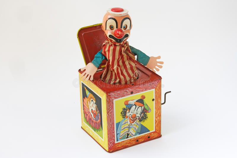 Surprise music box toy. A vintage surprise music box with clown background isolated royalty free stock photography