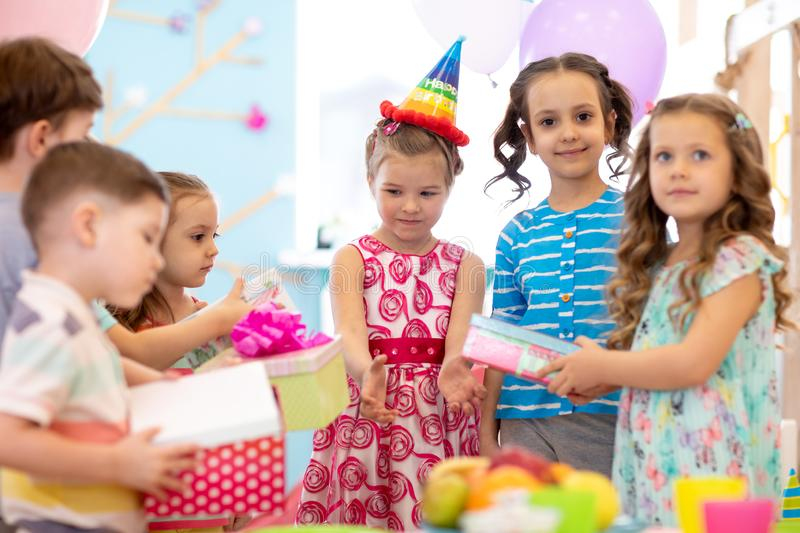 Portrait of a young beautiful girl wearing cone cap receiving happily her birthday present from friends. Surprise. Portrait of a young beautiful girl wearing stock photo