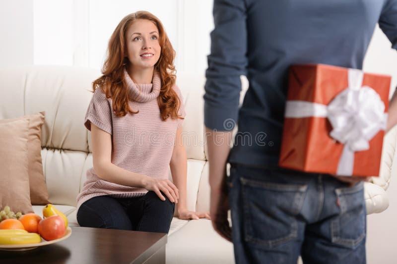 Surprise pour elle. Belle jeune femme s'asseyant au whi de divan photo stock