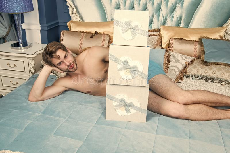 Surprise for sweetheart. Gifts for darling. Birthday morning. Romantic surprise. Valentines day celebration. Sexy. Surprise for female. Man in luxury bedroom royalty free stock photo