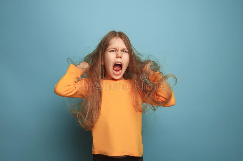 The surprise. Teen girl on a blue background. Facial expressions and people emotions concept stock images