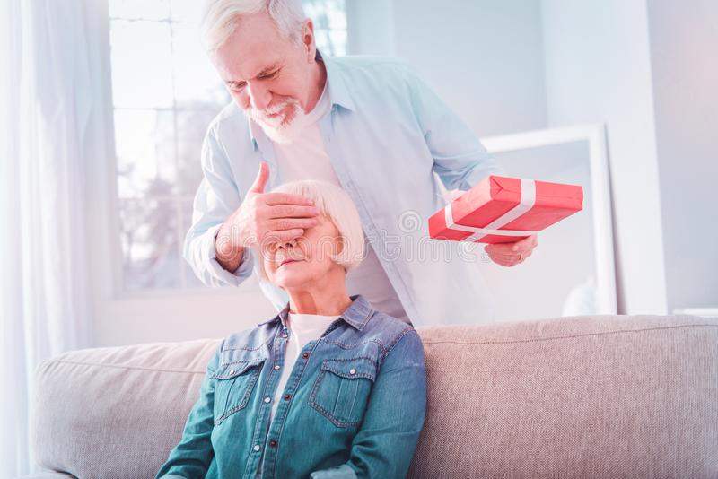Bearded retired man closing eyes of his woman making surprise for her royalty free stock image