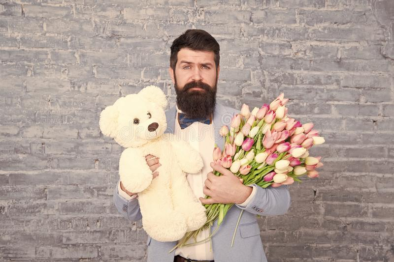 Surprise will melt her heart. Romantic man with flowers and teddy bear. Romantic gift. Macho getting ready romantic date. Man wear blue tuxedo bow tie hold royalty free stock photo