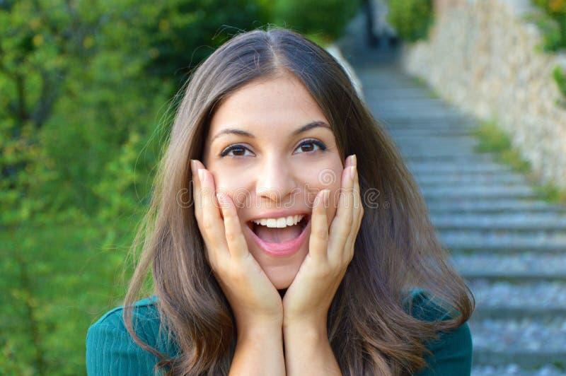 Surprised激发举行她的面孔陈列微笑的少妇 免版税图库摄影