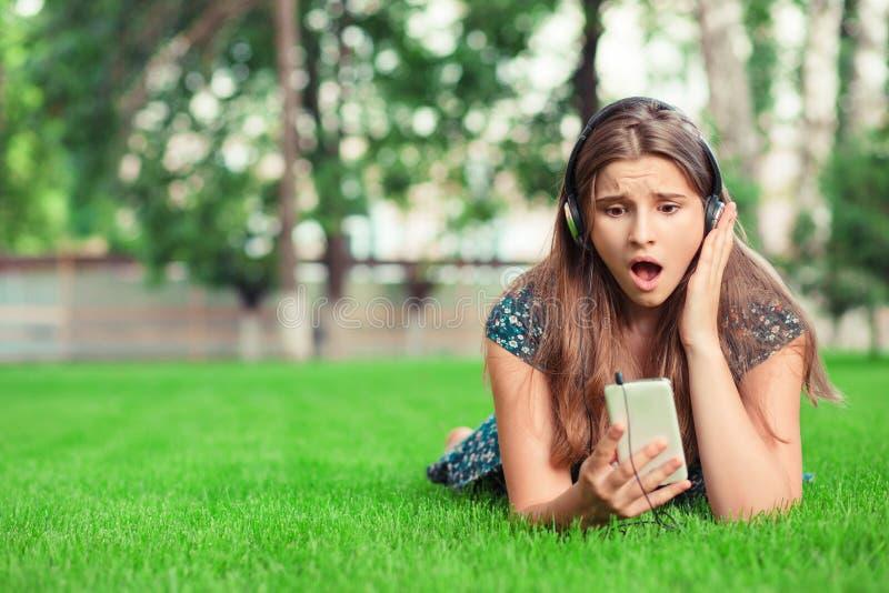 Surprised сотрясло молодую женщину смотря телефон стоковые изображения