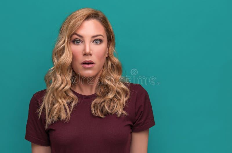 蓝色背景的一个可爱的金发碧眼的女人通过宽张她的眼睛和嘴惊奇或冲击 库存照片