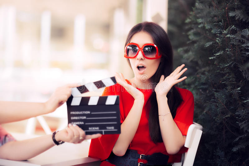 Surprised Actress with Oversized Sunglasses Shooting Movie Scene. Diva in red dress and big shades starring in an artistic film stock photos