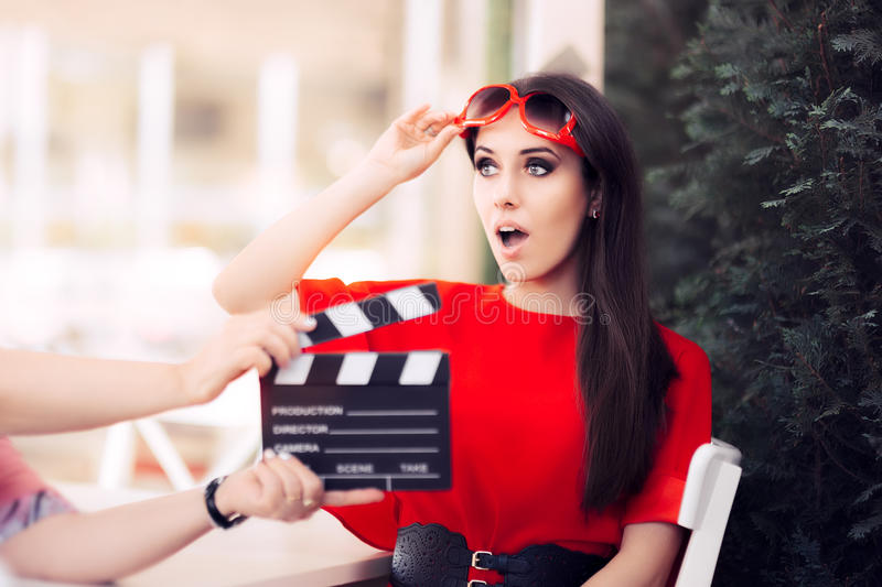 Surprised Actress with Oversized Sunglasses Shooting Movie Scene. Diva in red dress and big shades starring in an artistic film stock photo