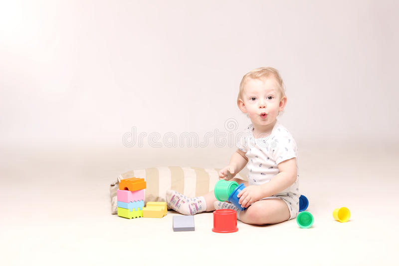 Surprised adorable baby boy sitting on the floor and playing with his toys. Shot of a surprised cute baby boy sitting on the floor and playing with his toys stock photos