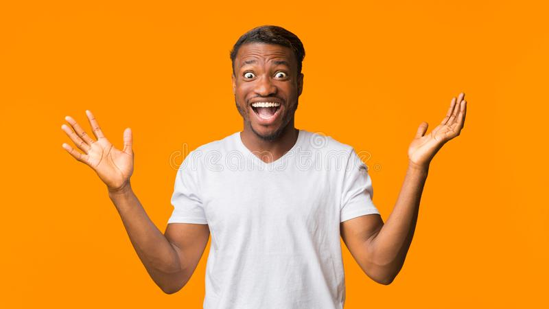 Surprised African American Man Shouting Looking At Camera, Studio, Panorama. Wow. Surprised African American Man Shouting Looking At Camera Standing Over Orange stock photo