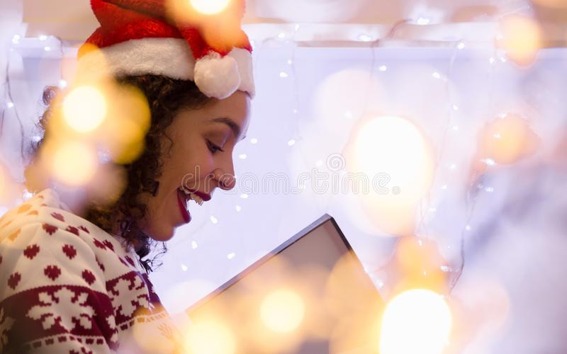 African American woman with Santa Claus hat and Christmas sweater opens gift box at home. blurred background with bokeh. Surprised African American woman with royalty free stock images