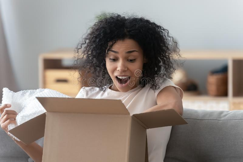 Surprised African American woman unpacking parcel at home close up stock images