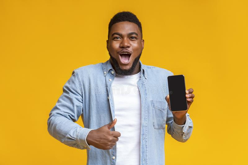 Surprised african man holding smartphone and showing thumb up. Wow, amazing app. Surprised african man holding smartphone with black screen and showing thumb up royalty free stock photo