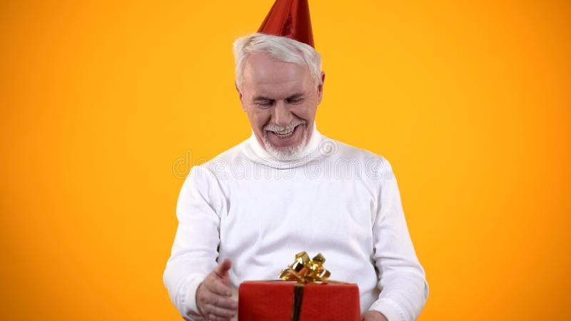 Surprised aged male looking at red gift box, feeling happy for present, birthday royalty free stock image