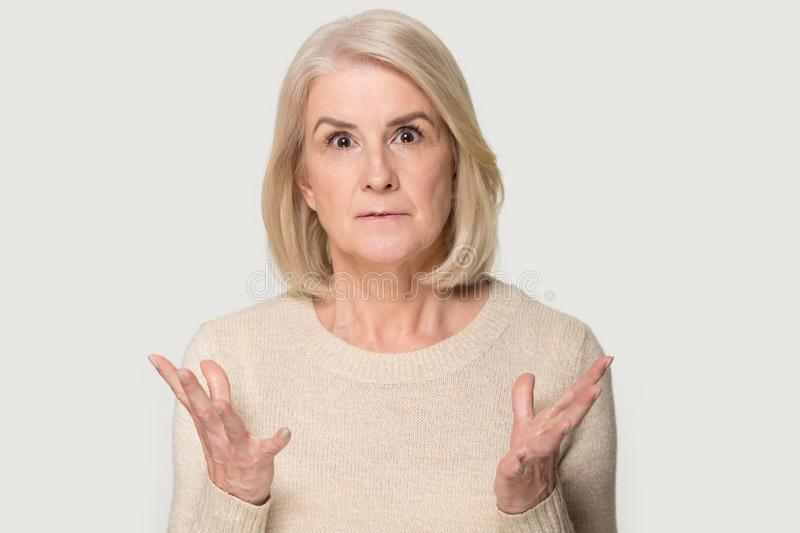 Surprised aged woman isolated on grey background shocked by deal stock photography