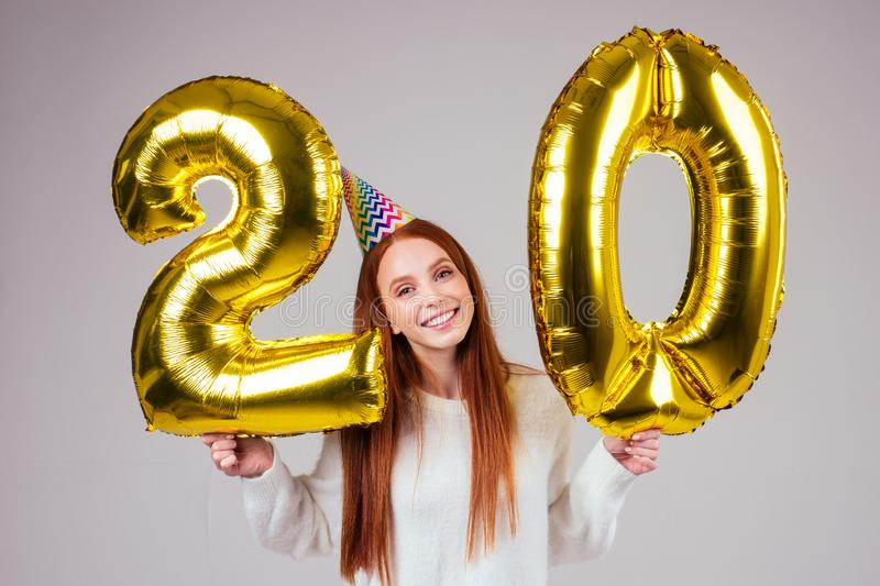 Surprised and amazed radhaired ginger woman with birthday cap horn holding ballons 20 years anniversary numeral in. Studio white background royalty free stock photo