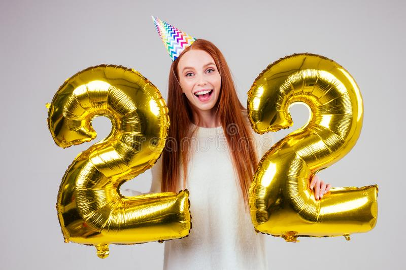 Surprised and amazed radhaired ginger woman with birthday cap horn holding ballons 22 years anniversary numeral in. Surprised and amazed radhaired ginger woman royalty free stock photo