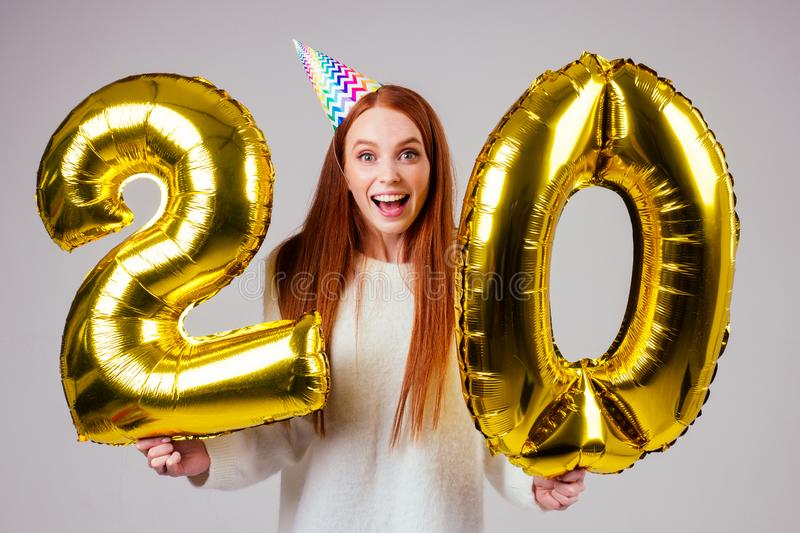 Surprised and amazed radhaired ginger woman with birthday cap horn holding ballons 20 years anniversary numeral in. Studio white background royalty free stock photos
