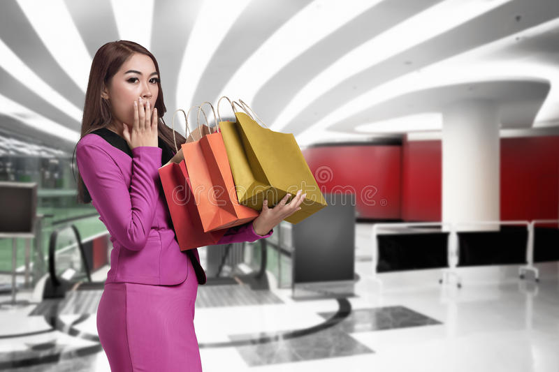 Surprised asian business woman holding in her hands many shopping bag royalty free stock images