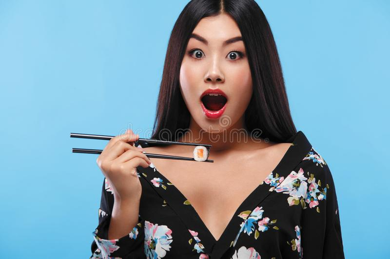 Surprised Asian woman eating sushi and rolls on a blue background. Black Friday sushi sale. stock photography