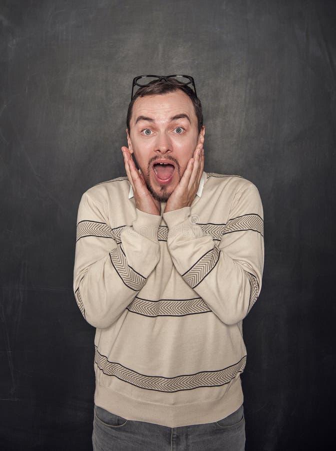 Surprised asustó al hombre divertido del profesor en la pizarra fotografía de archivo