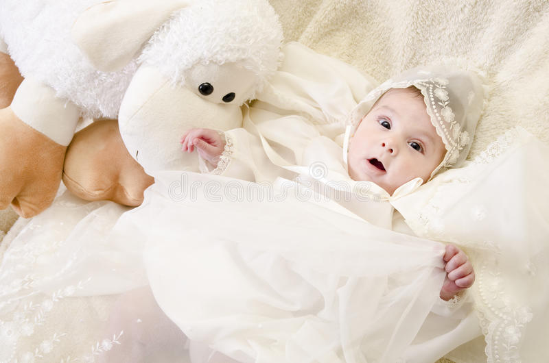 Surprised baby. Baptism clothes, lying baby and muppet stock photo