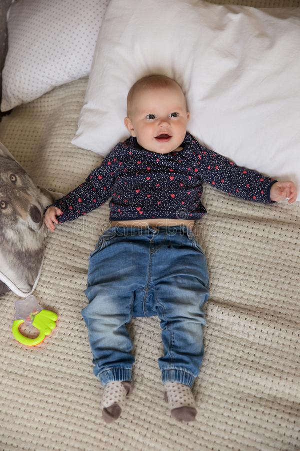 Surprised Baby Girl Lying on Bed and Looking Up royalty free stock photography